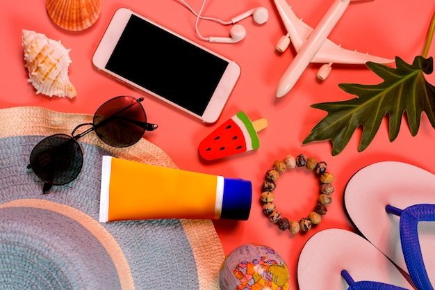 Bovenaanzicht van reiziger accessoires, tropisch palmblad en vliegtuig op roze achtergrond.