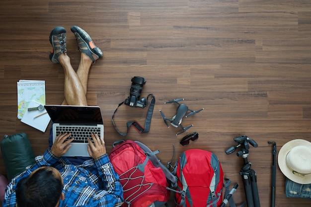 Bovenaanzicht van reiziger man plan en rugzak met werkende laptop