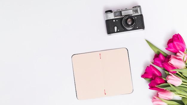 Bovenaanzicht van retro camera; tulp bloemen; en lege kaart tegen witte achtergrond