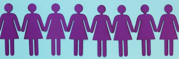 Bovenaanzicht van rij papier vrouwen hand in hand voor vrouwendag