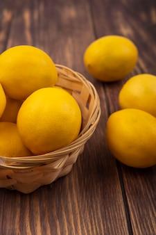 Bovenaanzicht van rijk aan vitamine c citroenen op een emmer met citroenen geïsoleerd op een houten muur