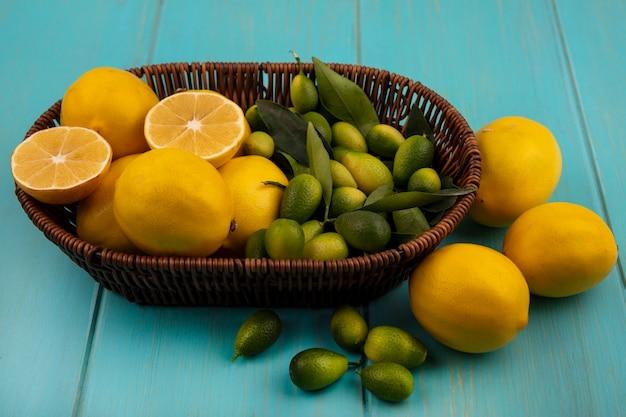 Bovenaanzicht van rijk aan vitamines fruit zoals citroenen en kinkans op een emmer met citroenen geïsoleerd op een blauwe houten muur
