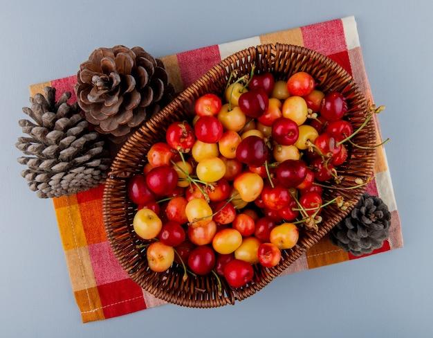 Bovenaanzicht van rijp regenachtiger cherriesin een rieten mand en kegels op geruite servet op grijs