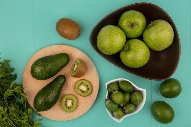 Bovenaanzicht van rijpe avocado's met plakjes kiwi op een houten keukenbord met feijoas op een kom met appels op een kom met limoenen geïsoleerd op een blauwe muur