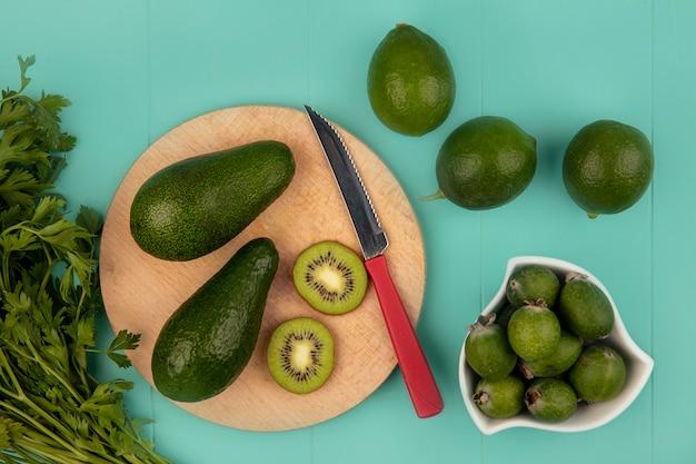 Bovenaanzicht van rijpe avocado's op een houten keukenbord met mes met feijoas op een kom met limoenen geïsoleerd op een blauwe muur