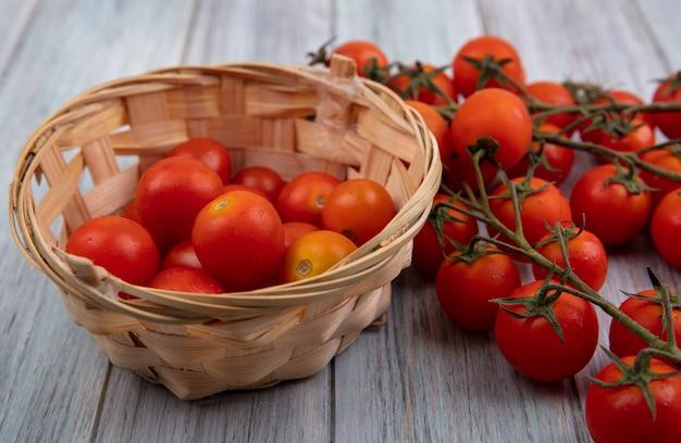 Bovenaanzicht van rijpe biologische tomaten op een emmer met trostomaten geïsoleerd op een grijze houten achtergrond