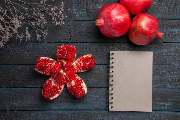 Bovenaanzicht van rijpe granaatappels rijpe gepilde granaatappel tussen drie granaatappels boomtakken en wit notitieboekje op donkere achtergrond