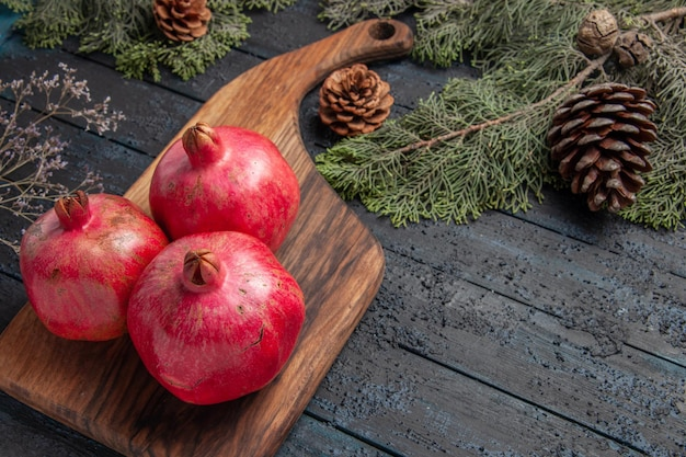 Bovenaanzicht van rijpe granaatappels rode granaatappels op snijplank naast de vuren takken met kegels op grijze tafel