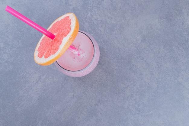 Bovenaanzicht van rijpe grapefruit met glas sap op grijze achtergrond.