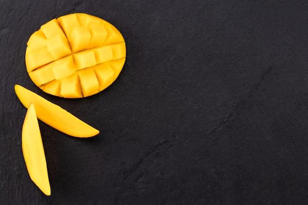 Bovenaanzicht van rijpe mango in tweeën gesneden en in blokjes gesneden op donkere leisteen.