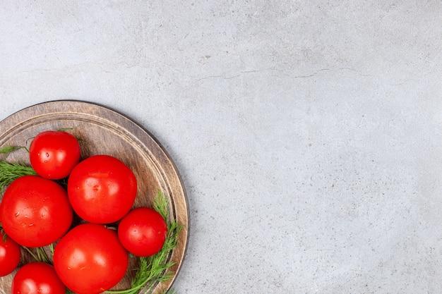 Bovenaanzicht van rijpe rode tomaten in houten bord.