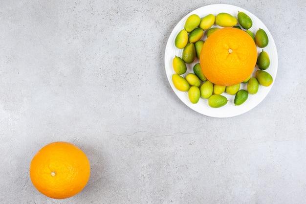 Bovenaanzicht van rijpe sinaasappel met stapel kumquats op witte plaat.