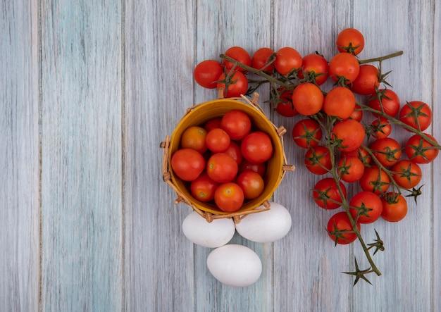Bovenaanzicht van rijpe tomaten op een emmer met trostomaten en eieren geïsoleerd op een grijze houten achtergrond met kopie ruimte