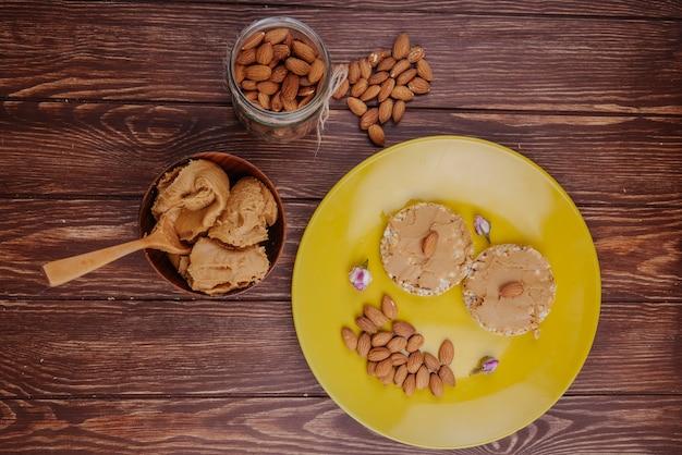 Bovenaanzicht van rijst cracker met pindakaas boter amandel in een glazen pot en een kom met pindakaas op houten achtergrond