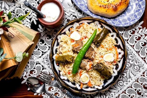 Bovenaanzicht van rijst schotel plaat gegarneerd met druivenbladeren dolma gekookte eieren en lam