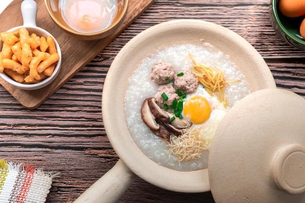 Bovenaanzicht van rijstepap in geopende aarden pot serveren met knapperige gefrituurde stok op het oppervlak