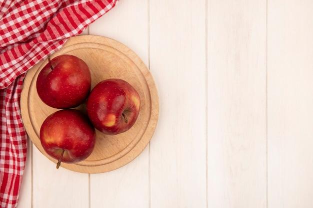 Bovenaanzicht van rode appels op een houten keukenbord op een rood geruite doek op een wit houten oppervlak met kopie ruimte