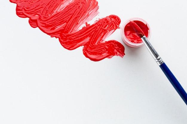Bovenaanzicht van rode aquarel met borstel