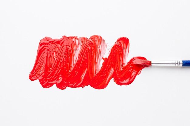Bovenaanzicht van rode aquarel op borstel
