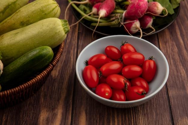 Bovenaanzicht van rode biologische tomaten op een kom met verse groenten zoals courgettes, komkommer op een emmer op een houten oppervlak