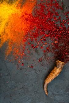 Bovenaanzicht van rode chili en sumak poeder specerijen met curry op zwart