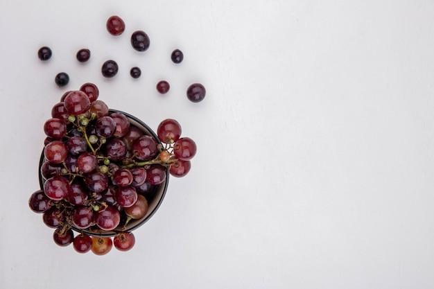 Bovenaanzicht van rode druif in kom en op witte achtergrond met kopie ruimte