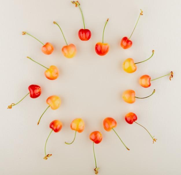 Bovenaanzicht van rode en gele kersen in ronde vorm op wit