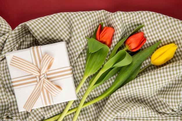 Bovenaanzicht van rode en gele kleur tulpen en een huidige doos gebonden met strik op geruite stof op rode tafel
