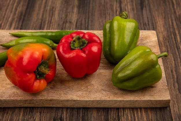 Bovenaanzicht van rode en groene paprika op een houten keukenbord op een houten achtergrond