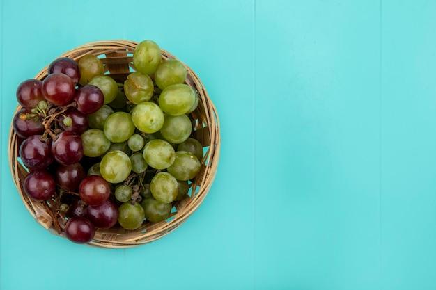 Bovenaanzicht van rode en witte druiven in mand op blauwe achtergrond met kopie ruimte