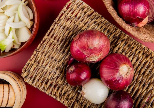 Bovenaanzicht van rode en witte uien in mand plaat met gesneden witte in kom en zwarte peper zaden op rode ondergrond