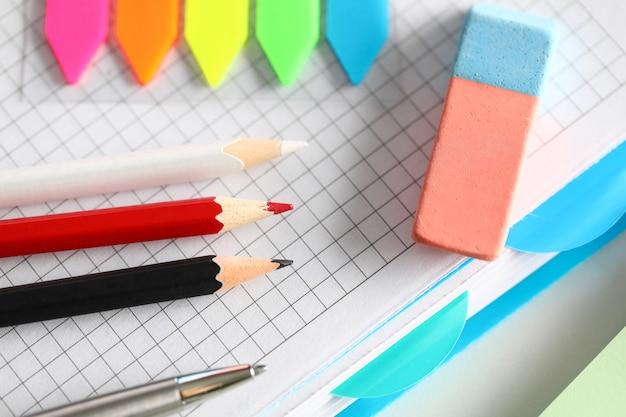 Bovenaanzicht van rode en zwarte potloden. zilveren pen en gum. kleurrijke bladwijzers op desktop. leeg notitieboekblad. papier voor notities en creatieve ideeën. kantoorbenodigdheden concept