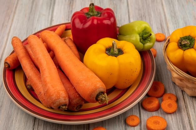 Bovenaanzicht van rode gele en groene paprika op een bord met wortelen met gele paprika op een emmer op een grijze houten ondergrond