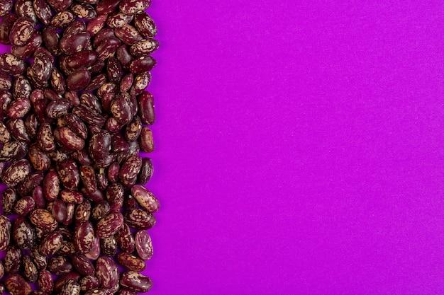Bovenaanzicht van rode gespikkelde bruine bonen met kopie ruimte op paars