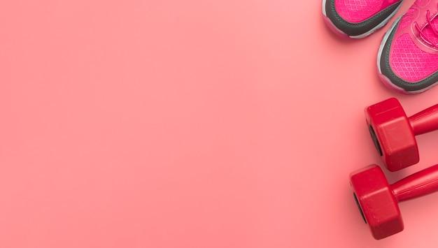 Bovenaanzicht van rode gewichten met sneakers en kopie ruimte