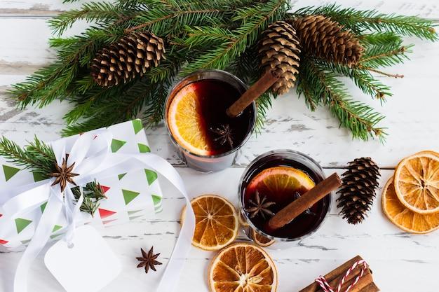 Bovenaanzicht van rode glühwein met droge sinaasappelen op sparren takken met kegels. kerst feestelijke drank, bovenaanzicht