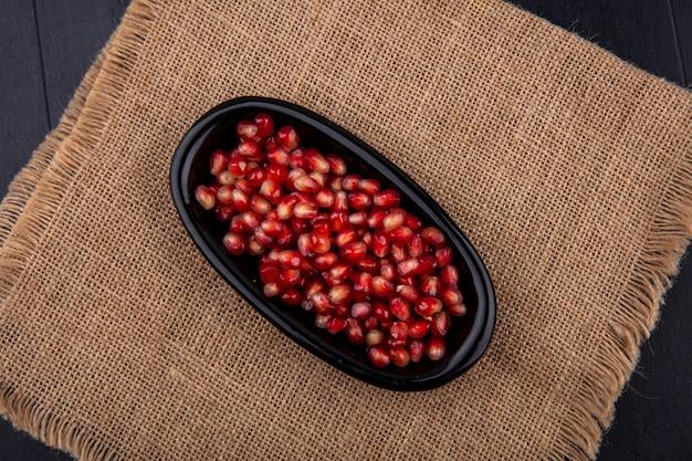 Bovenaanzicht van rode granaatappel zaden in een zwarte plaat op zak doek oppervlak
