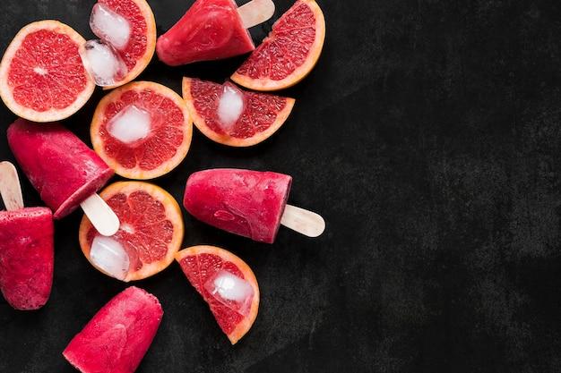 Bovenaanzicht van rode grapefruit ijslollys met kopie ruimte