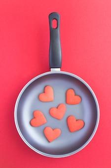 Bovenaanzicht van rode harten vormige koekjes in een koekenpan