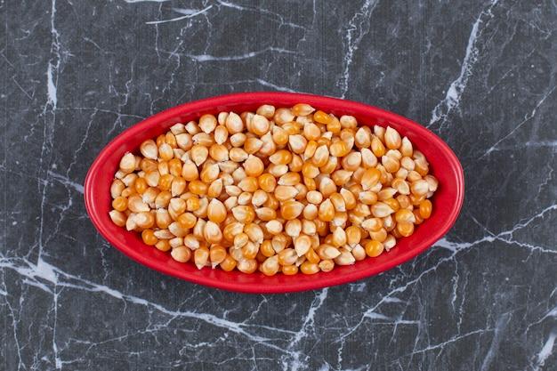Bovenaanzicht van rode keramische kom vol met maïs zaden.