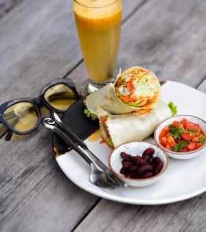 Bovenaanzicht van rode lippenstift, voedsel en paarse bloem op houten tafel. foto van grote plaat met smakelijke salade en bonen die zich naast glas smoothie bevinden.
