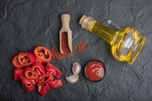Bovenaanzicht van rode peper plakjes met olie, ketchup en knoflook op zwarte achtergrond.