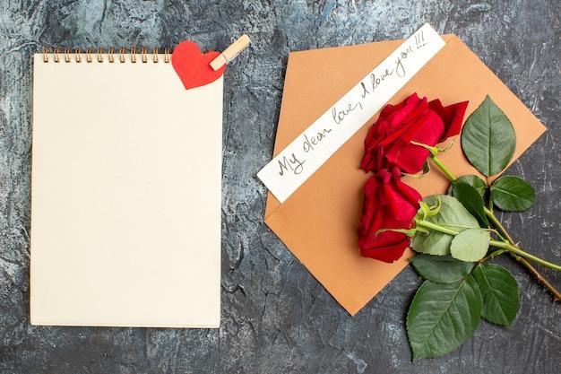 Bovenaanzicht van rode rozen en envelop met liefdesbrief en spiraalvormig notitieboekje op ijzige donkere achtergrond
