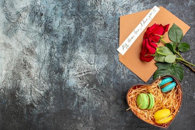 Bovenaanzicht van rode rozen en envelop met liefdesbrief en verschillende macarons op ijzige donkere achtergrond