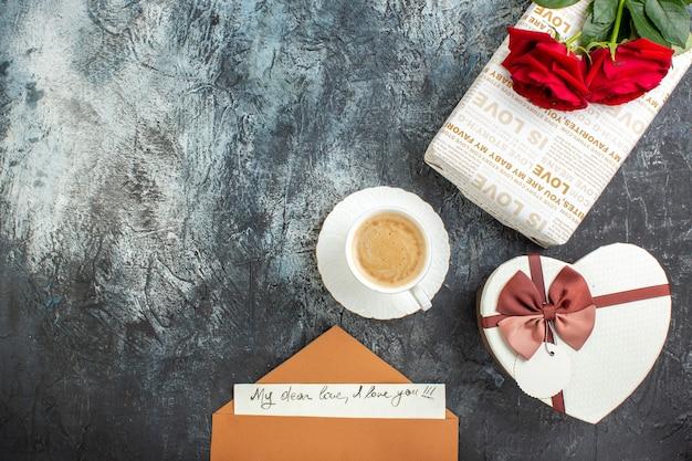 Bovenaanzicht van rode rozen en mooie geschenkdozen envelop met brief een kopje koffie voor geliefde op ijzige donkere achtergrond