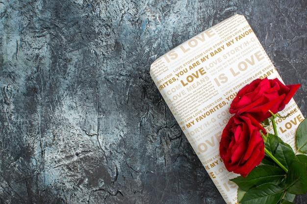 Bovenaanzicht van rode rozen op mooie geschenkdoos aan de linkerkant op donkere achtergrond