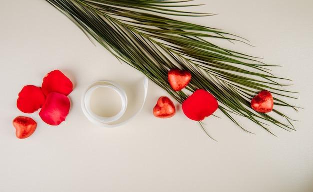 Bovenaanzicht van rode rozenblaadjes, hartvormige chocoladesuikergoed verpakt in rode folie en palmblad met lint op witte tafel