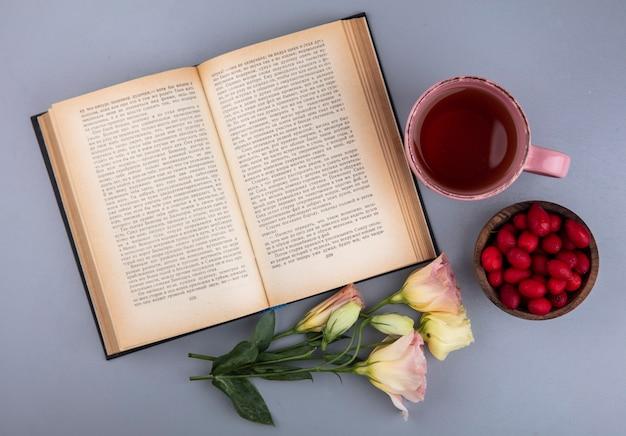 Bovenaanzicht van rode verse cornel bessen op een kom met een kopje thee op een grijze achtergrond