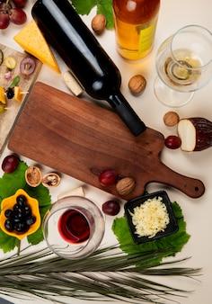 Bovenaanzicht van rode wijn en witte wijn met olijf walnoot druiven snijplank geraspte parmezaanse kaas op witte tafel versierd met bladeren