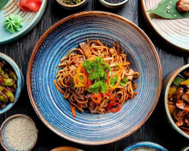 Bovenaanzicht van roergebakken noedels met groenten en garnalen in een plaat op houten tafel